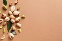 Composición con las nueces de pistacho orgánicas en el fondo del color, endecha plana fotografía de archivo libre de regalías