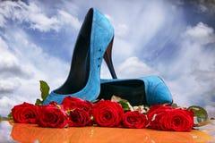 Composición con las rosas rojas y los zapatos femeninos azules Imagen de archivo libre de regalías