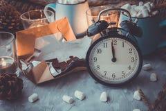 Composición con las tazas, reloj, velas, chocolate, melcocha, cono del día de fiesta de la Navidad y del Año Nuevo del pino en el Fotos de archivo libres de regalías
