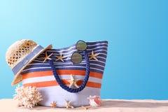 Composición con los accesorios de la playa en la arena contra fondo del color Imagenes de archivo
