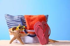 Composición con los accesorios de la playa en la arena contra fondo del color Foto de archivo libre de regalías