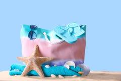 Composición con los accesorios de la playa en la arena contra fondo del color Imagen de archivo libre de regalías