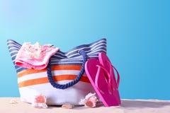 Composición con los accesorios de la playa en la arena contra fondo del color Fotos de archivo