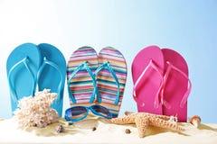 Composición con los accesorios de la playa en la arena contra fondo del color Fotos de archivo libres de regalías