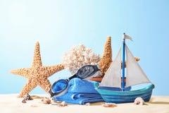 Composición con los accesorios de la playa en la arena contra fondo del color Foto de archivo