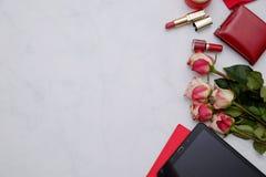 Composición con los artículos rojos: flores y accesorios femeninos lindos en el fondo blanco Concepto del blogger de la mujer Imágenes de archivo libres de regalías