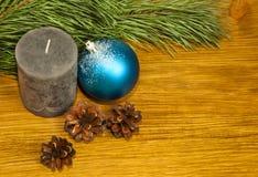 Composición con los conos de abeto y vela gris en fondo de madera Foto de archivo