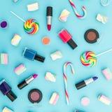 Composición con los cosméticos femeninos y el caramelo brillante en fondo azul Visión superior Endecha plana Escritorio femenino  Imagenes de archivo