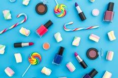 Composición con los cosméticos femeninos y el caramelo brillante en fondo azul Visión superior Endecha plana Escritorio femenino  Fotos de archivo