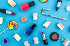 Composición con los cosméticos femeninos y el caramelo de azúcar brillante en fondo azul Visión superior Endecha plana Escritorio Imagen de archivo libre de regalías
