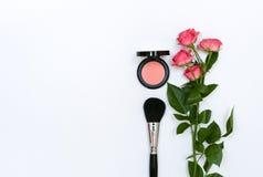 Composición con los cosméticos, los cepillos, los shadoes y las flores del maquillaje en el fondo blanco Imagen de archivo libre de regalías