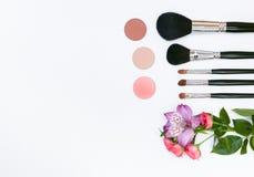 Composición con los cosméticos, los cepillos, los shadoes y las flores del maquillaje en el fondo blanco Imágenes de archivo libres de regalías