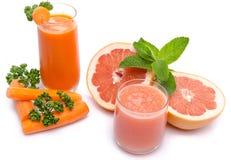 Composición con los jugos de la zanahoria y de pomelo imagen de archivo
