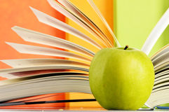Composición con los libros de tapa dura y la manzana en la biblioteca Fotografía de archivo
