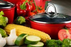 Composición con los potes de acero rojos y la variedad de verduras frescas Imagen de archivo libre de regalías