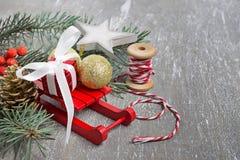 Composición con los trineos, rama del abeto, caja de la Navidad de regalo Fotografía de archivo libre de regalías
