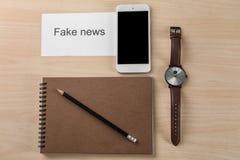 Composición con NOTICIAS FALSAS de la frase y teléfono en fondo de madera fotografía de archivo libre de regalías