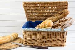 Composición con pan y rollos en cesta de mimbre en el fondo blanco imágenes de archivo libres de regalías