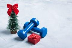 Composición con pesas de gimnasia, caja de regalo roja, Cristo del deporte de la Navidad foto de archivo libre de regalías