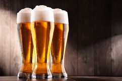Composición con tres vidrios de cerveza de cerveza dorada Foto de archivo