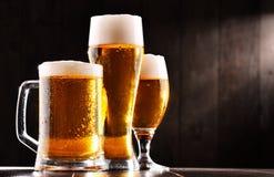 Composición con tres vidrios de cerveza de cerveza dorada Foto de archivo libre de regalías