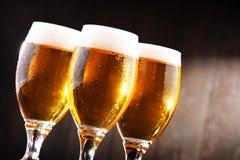 Composición con tres vidrios de cerveza de cerveza dorada Fotos de archivo libres de regalías