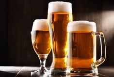 Composición con tres vidrios de cerveza de cerveza dorada Imagen de archivo libre de regalías