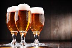 Composición con tres vidrios de cerveza de cerveza dorada Imagen de archivo