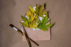Composición con una letra y hojas de arce amarillas Imagen de archivo