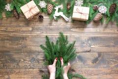 Composición creativa del marco de la Navidad Mano femenina que lleva a cabo la rama spruce para hacer en el fondo de madera Fotografía de archivo libre de regalías