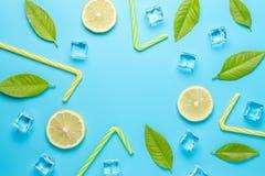 Composición creativa del verano con los cubos cortados del limón, de la paja y de hielo en fondo azul Concepto mínimo de la bebid fotos de archivo