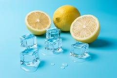 Composición creativa del verano con los cubos cortados del limón y de hielo en fondo azul Concepto mínimo de la bebida fotos de archivo libres de regalías