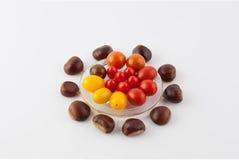 Composición culinaria de las castañas y de los tomates de cereza Fotografía de archivo
