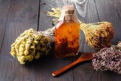 Composición de botellas con aceite en la tabla de madera Fotos de archivo