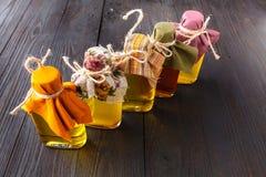 Composición de botellas con aceite en la tabla de madera Fotografía de archivo