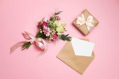 Composición de día de San Valentín: ramo de flores, caja de regalo con el arco de la cinta, sobre de Kraft con endecha de la tarj foto de archivo libre de regalías