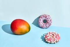 Composición de frutas y dulces frescos, dos anillos de espuma y mango jugoso imágenes de archivo libres de regalías
