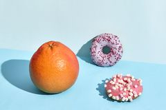 Composición de frutas y dulces frescos, dos anillos de espuma y pomelo jugoso imagen de archivo libre de regalías