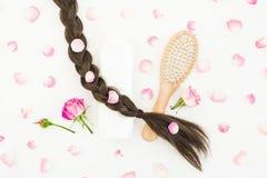 Composición de la belleza con el peine para diseñar del pelo, el champú y las flores rosadas en el fondo blanco Endecha plana, vi Fotografía de archivo libre de regalías