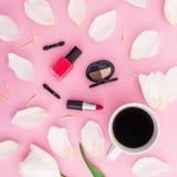 Composición de la belleza con las flores de los tulipanes, la taza de café y los cosméticos en fondo rosado Visión superior Endec Fotografía de archivo libre de regalías