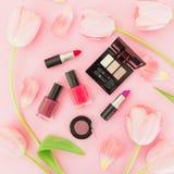 Composición de la belleza con las flores de los tulipanes y los cosméticos femeninos en fondo rosado Visión superior Endecha plan Imagenes de archivo