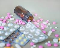 Composición de la botella y de las píldoras de la medicina en fondo gris Fotos de archivo libres de regalías