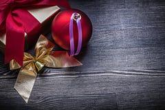 Composición de la caja de regalo brillante del arco de la bola en de madera Imagen de archivo