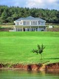 Composición de la casa y del árbol al lado del lago Fotos de archivo libres de regalías