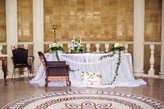 Composición de la flor de la boda con las hojas en la tabla Imágenes de archivo libres de regalías