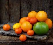 Composición de la fruta cítrica en fondo de madera: mandarinas, naranjas, encanto, limón Vista lateral Imágenes de archivo libres de regalías