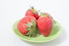 Composición de la fruta, fresas en una placa verde aislada en un w Imagen de archivo libre de regalías