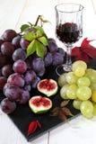Composición de la fruta: uvas, higos y vidrio de vino rojo Foto de archivo libre de regalías