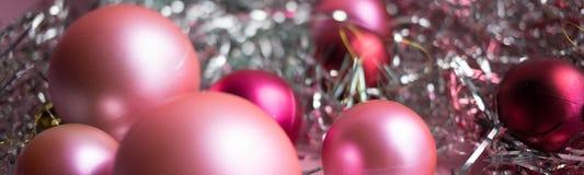 Composición de la Navidad Bolas rojas y rosadas de la Navidad, decoraciones de la malla en fondo rosado foto de archivo