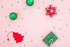 Composición de la Navidad Caja de regalo de la Navidad, juguetes y confeti que brilla en fondo rosado Endecha plana, visión super foto de archivo libre de regalías